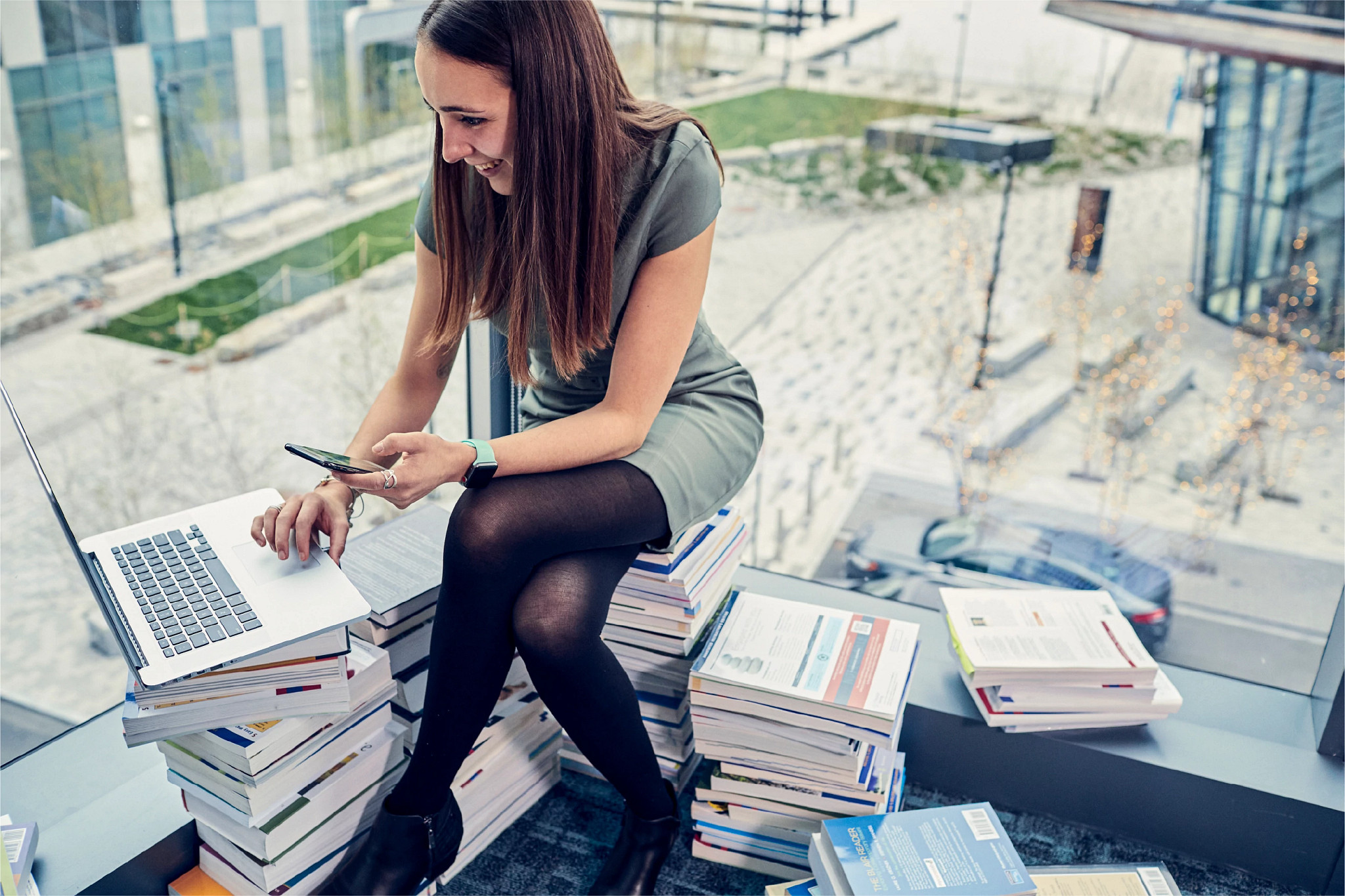 Dana T., Digital Communications Manager, works on her phone while sitting on a pile of books to tell how Cengage is reinventing education.