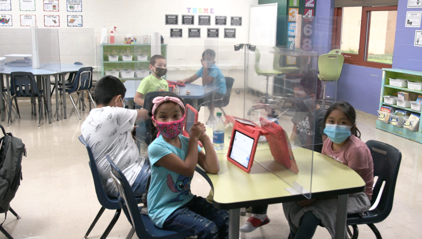Six diverse, young children eat lunch in a school cafeteria with plexiglass separating them, while all wearing masks. This is promoting integrating social emotional learning and diversity inclusion in the classroom and at home.