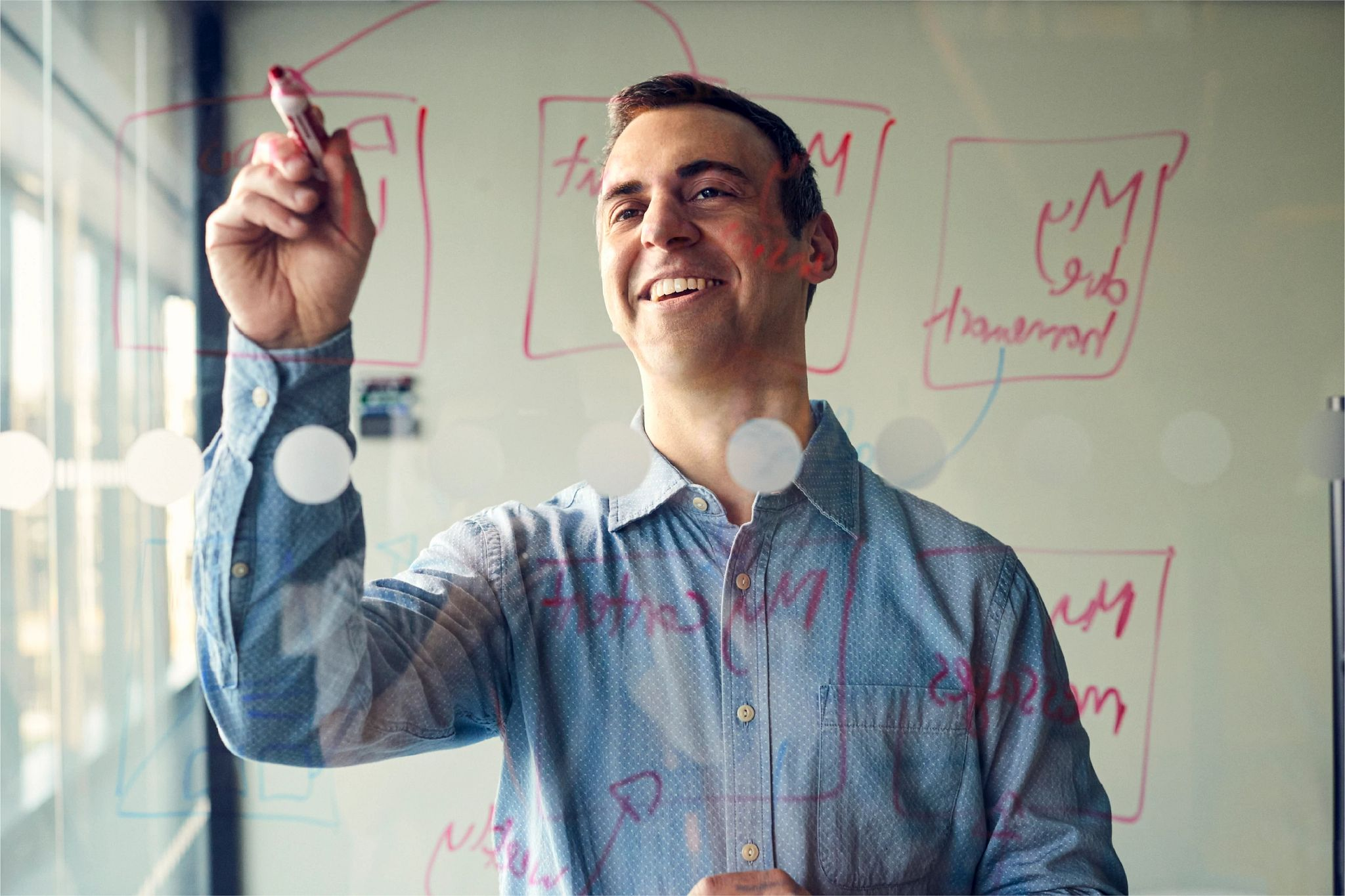 Matt N., Vice President, Technical Product Management, explores innovative approaches to education technology while writing on a whiteboard.