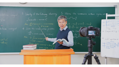 teacher standing in front of a chalkboard teaching into a camera
