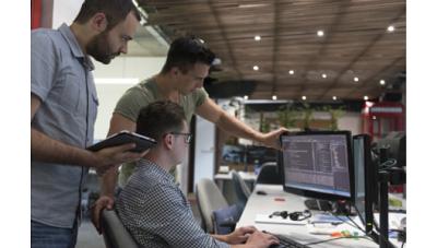 Three men working looking at a desktop computer screen