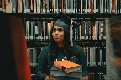 A young woman dressed in cap and gown holds a stack of books while sitting in a library with a wall of books behind her.