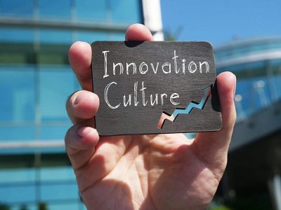 A hand holds a small, wooden sign with the white words: Innovation Culture written on it, representing culture being king in our virtual world.